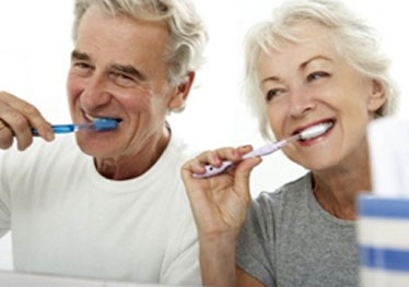 elderly couple brushing their teeth together