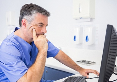 Dentist concentrating as he considers safety information on computer